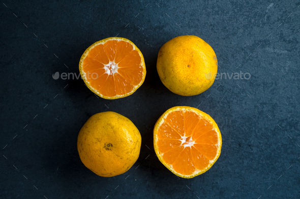 Four halves of an orange on a blue stone - Stock Photo - Images