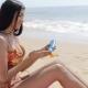 Woman Applying Cream on Beach