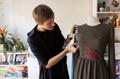 fashion designer with dummy making dress at studio