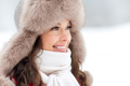 close up of happy woman in winter fur hat outdoors