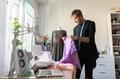 fashion designer with cloth making dress at studio