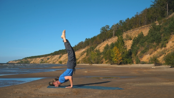 Strong Man Practicing Difficult Yoga Pose On The Beach By