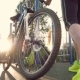 Girl Athlete Sits on a Bicycle and Somewhere He Leaves Detailed Pedals and Wheels Bike on Sunset - VideoHive Item for Sale