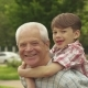 Little Boy Shows His Thumbs Up on His Grandpa's Back - VideoHive Item for Sale