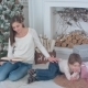 Mother Reading a Book for Her Little Son Lying Near Christmas Tree - VideoHive Item for Sale