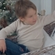Little Boy Arranging Christmas Pillows in His Wicker Sledge - VideoHive Item for Sale