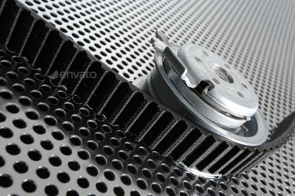 Bearing tensioner and timing belt on a metal surface - Stock Photo - Images
