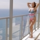 Content Woman in Swimsuit Posing on Balcony