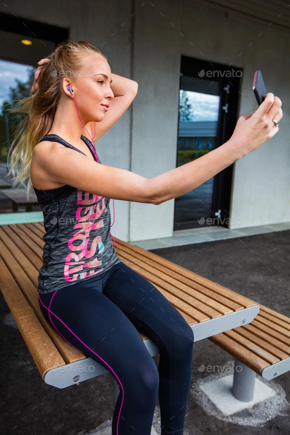 Young Woman In Sportswear Taking Selfie While Sitting On Bench - Stock Photo - Images