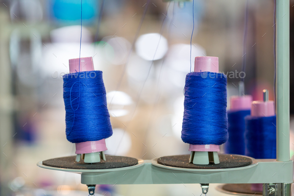 Spools of blue threads on sewing machine, factory - Stock Photo - Images