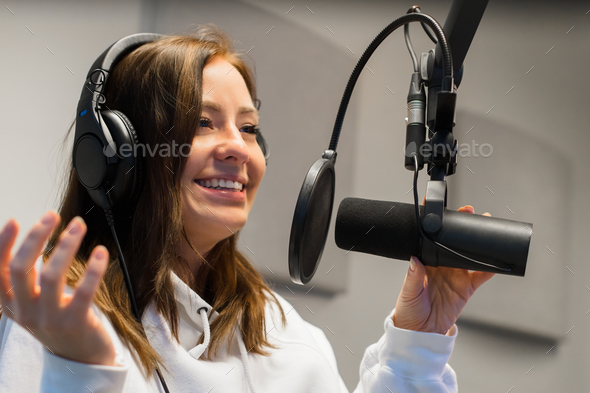 Close-up of a Female Jockey Communicating On Microphone In Radio Studio - Stock Photo - Images