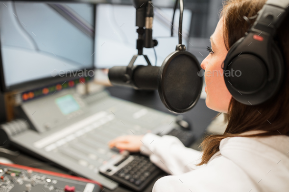 Jockey Wearing Headphones While Using Microphone In Radio Statio - Stock Photo - Images