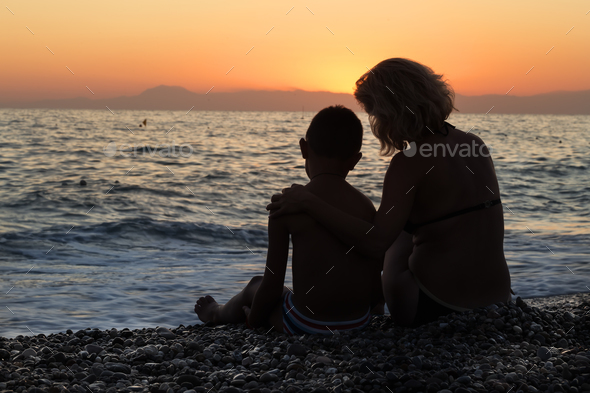 Silhouette of mom and son on seashore in evening - Stock Photo - Images