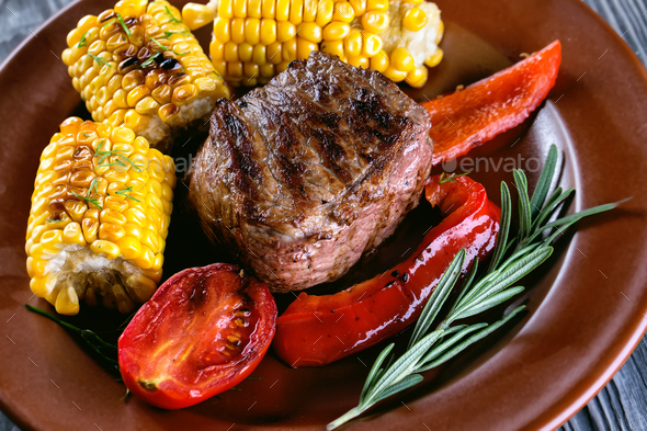 Piece of baked meat with vegetables and marinated on plate - Stock Photo - Images