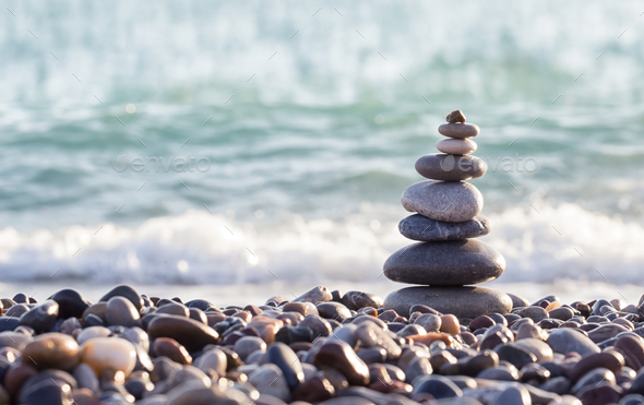 Pyramid of sea stones on pebbles of the sea shore - Stock Photo - Images