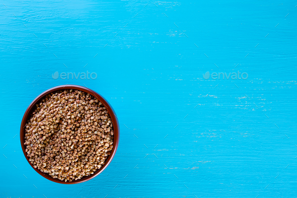 Clay brown bowl with raw buckwheat on blue background - Stock Photo - Images