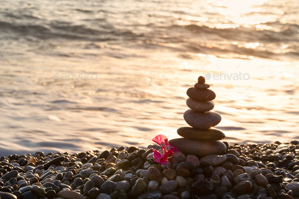 Pyramid of stones and red flower on the seashore - Stock Photo - Images