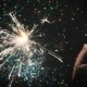 Woman Holds Firework Sparkler on Festive Backdrop - VideoHive Item for Sale