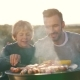 Father and Son Cook Sausages on Grill - VideoHive Item for Sale