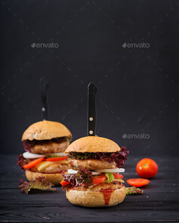 Big hamburger - Sandwich with chicken burger, cheese, onions, tomatoes and lettuce - Stock Photo - Images