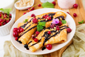 Pancakes with chocolate, honey, nuts and summer berries. Tasty breakfast