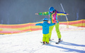 Father or instructor teaching little boy to ski