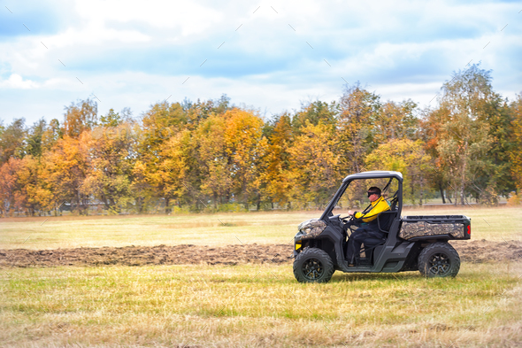 Hunting quad bike with driver in mask - Stock Photo - Images
