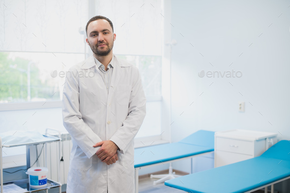 Smiling handsome doctor at hospital. Standing. Looking at camera. - Stock Photo - Images