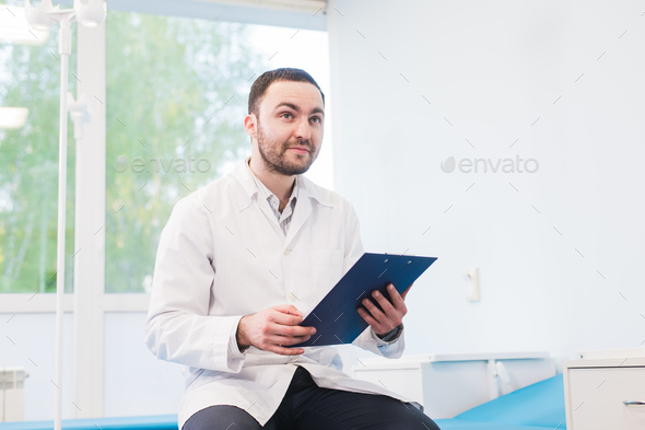 Cheerful young doctor holding a clipboard and gesturing with his hand at hospital ward - Stock Photo - Images