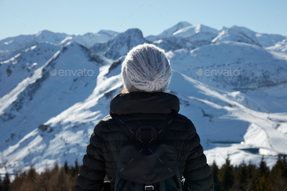 Woman with wool hat looking at mountains with snow in a sunny day - Stock Photo - Images