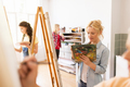 woman artist with easel painting at art school