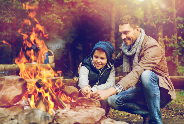 father and son roasting marshmallow over campfire - Stock Photo - Images
