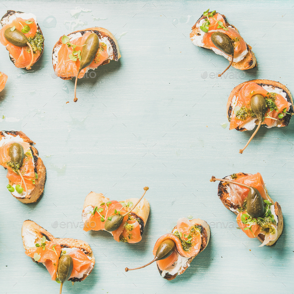 Crostini with smocked salmon, pesto sauce , watercress, capers. Blue background - Stock Photo - Images