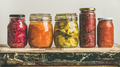 Autumn pickled colorful vegetables in jars placed in line