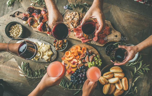 People having party sitting at table set with wine snacks - Stock Photo - Images