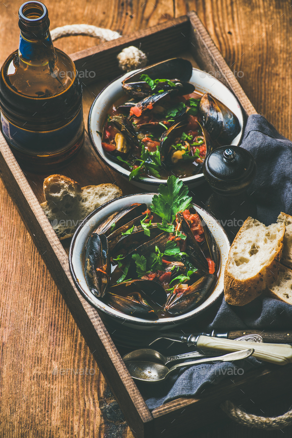 Belgian boiled mussels in tomato sauce and beer in bottle - Stock Photo - Images