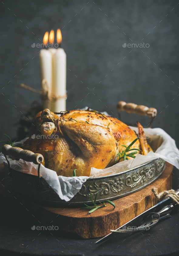 Christmas holiday table set with roasted whole chicken and candles - Stock Photo - Images