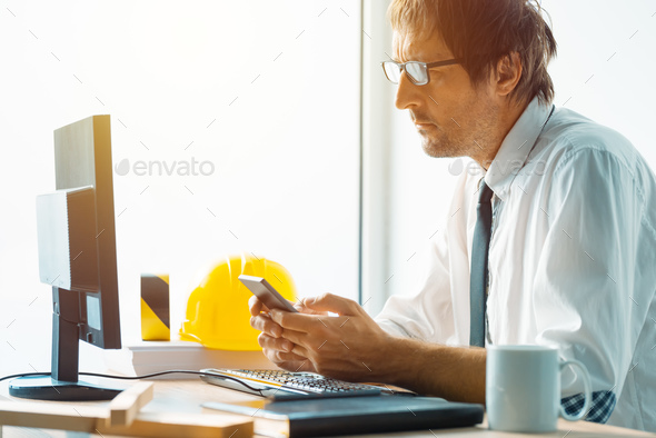 Architect and construction engineer working in office - Stock Photo - Images