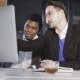 Two Men in the Office Communicate in Front of a Computer