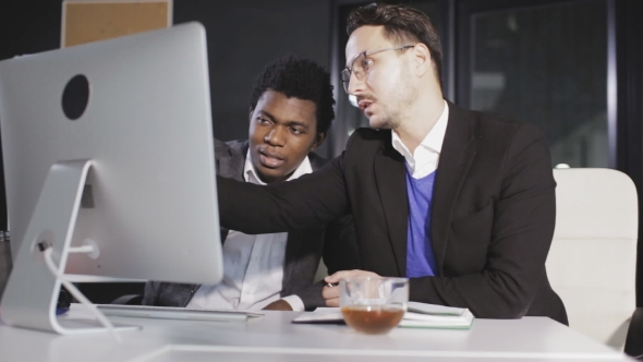 VideoHive Two Men in the Office Communicate in Front of a Computer 20792915