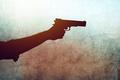 Hand with a gun on grunge background