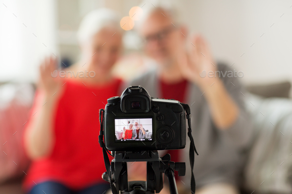 happy senior couple with camera recording video - Stock Photo - Images