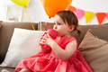 baby girl drinking from sippy cup at birthday
