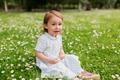 happy baby girl on green summer field