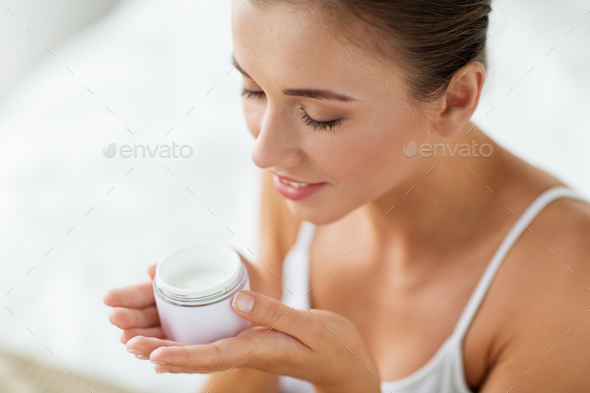 close up of happy woman holding and smelling cream - Stock Photo - Images