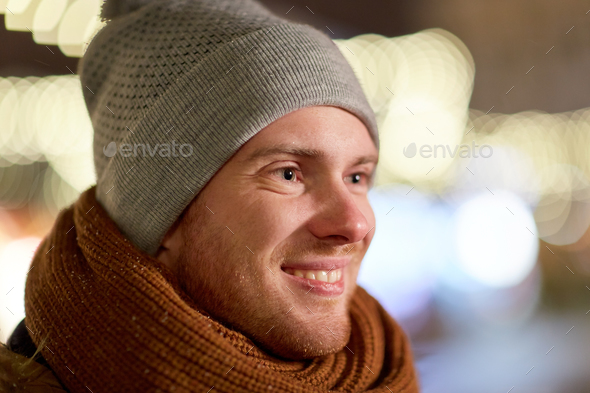 happy young man over christmas lights in winter - Stock Photo - Images