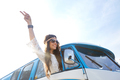 happy hippie woman showing peace in minivan car