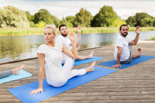 people making yoga in half lord of the fishes pose - Stock Photo - Images
