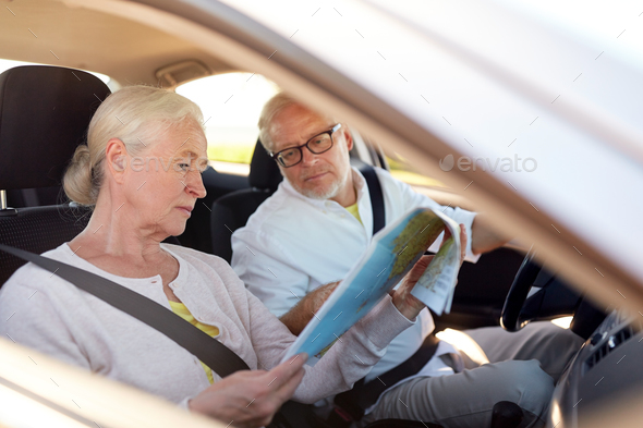 happy senior couple with map driving in car - Stock Photo - Images