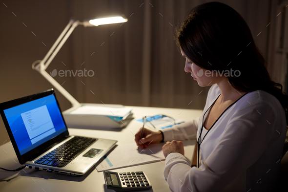 woman with calculator and papers at night office - Stock Photo - Images